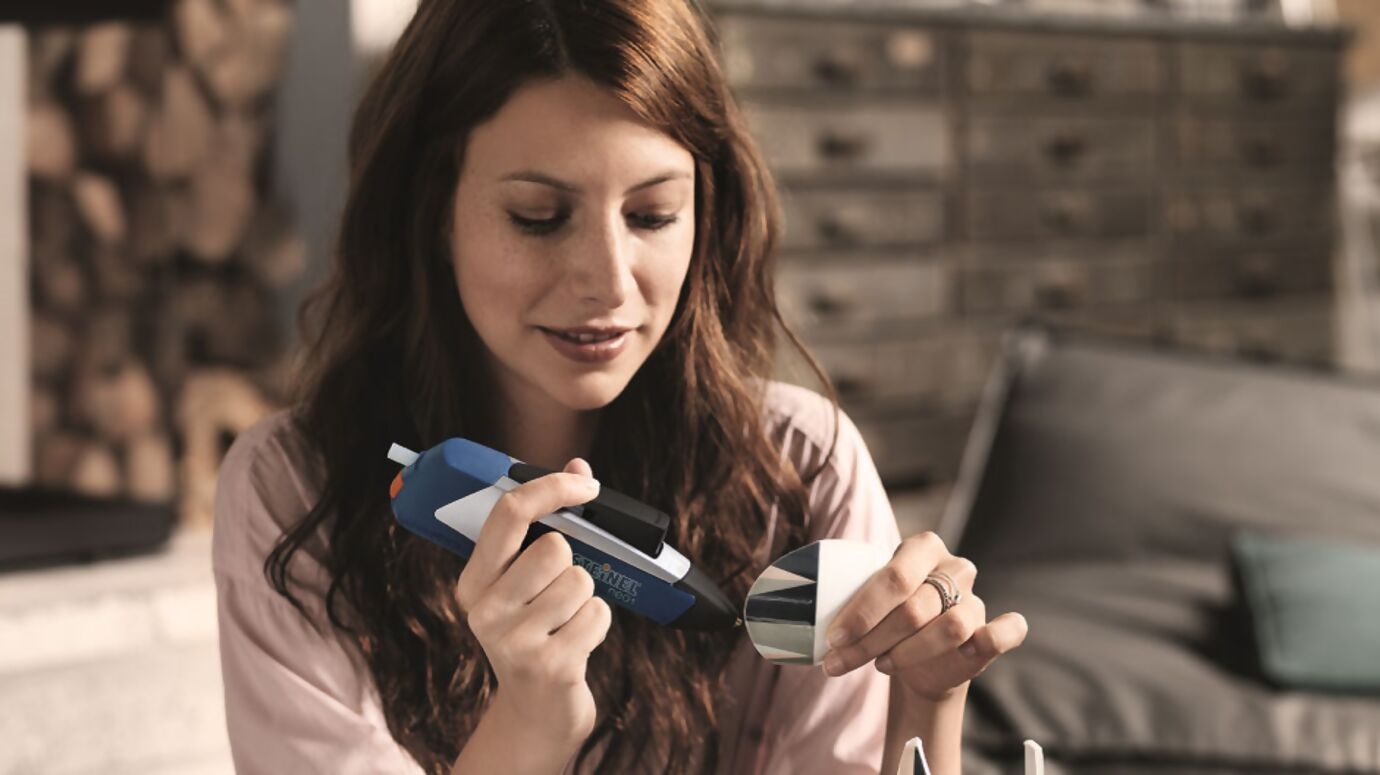 Frau repariert zerbrochene Vase mit der Heißklebepistole neo1