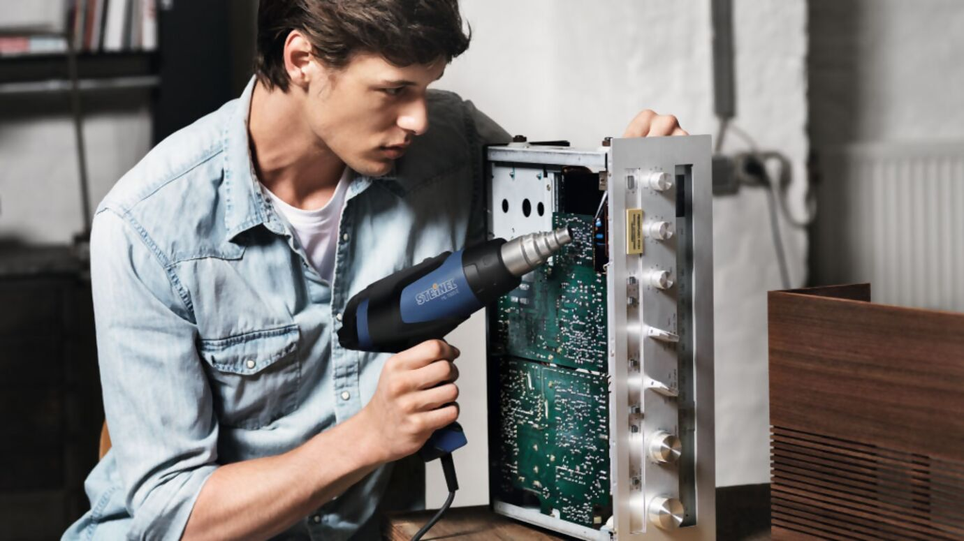 Mann repariert Platine mit Heißluft