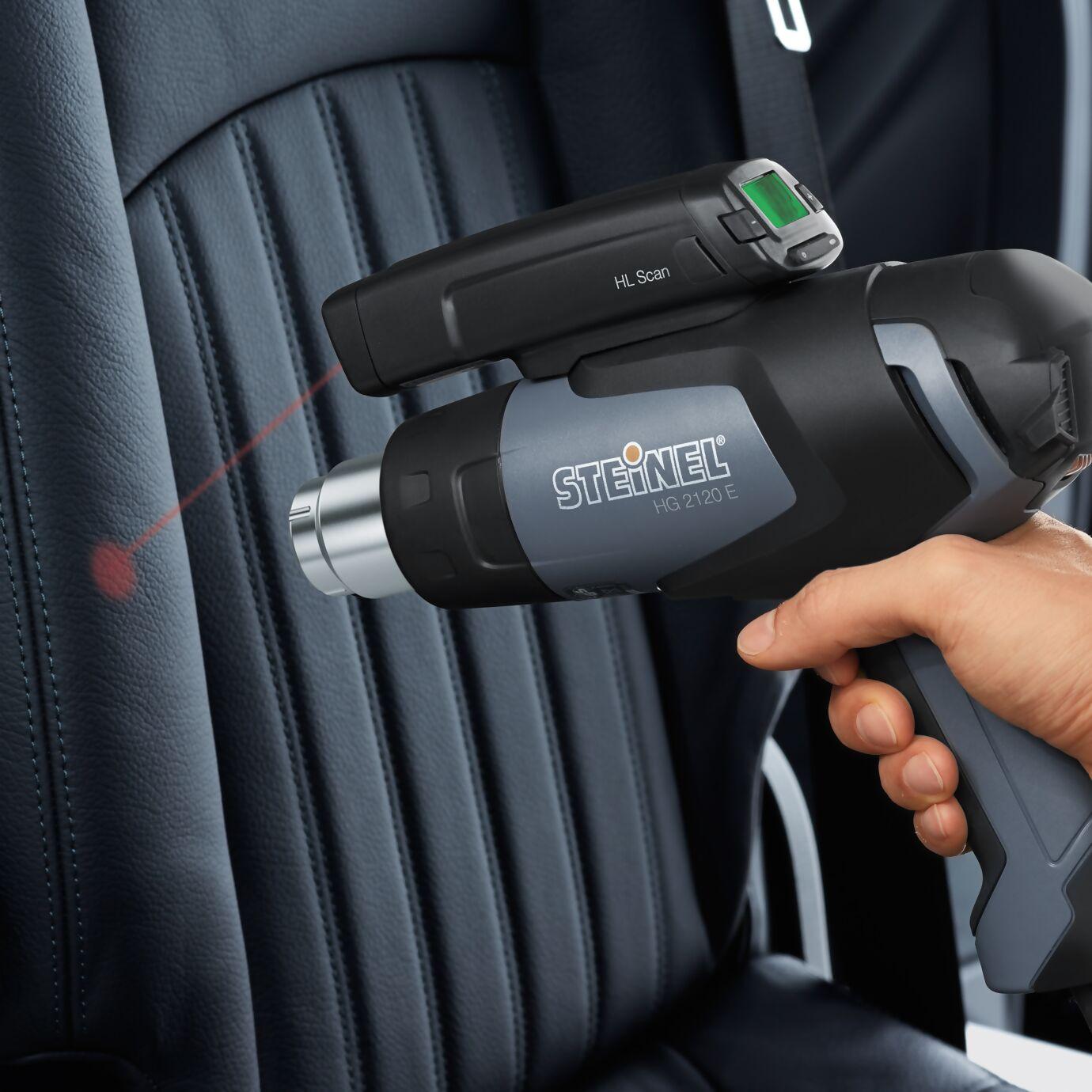 Heißluftgebläse in Verwendung zum Leder glätten von einem Autositz