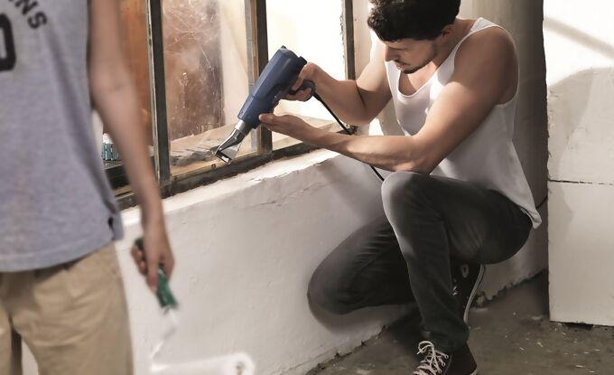 Heißluftgebläse wird von einem Arbeiter an Fensterarbeiten verwendet