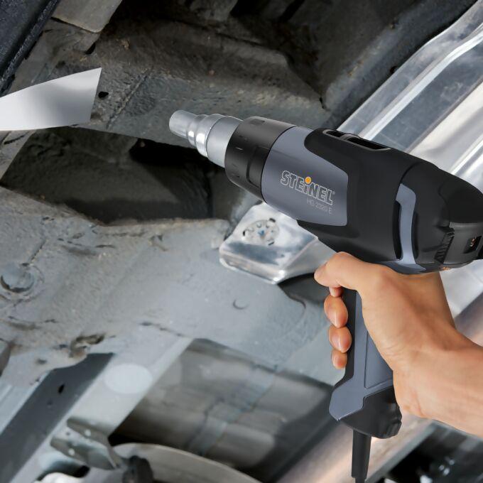 Anwendung eines Pistolengerätes beim Entfernen des Unterbodenschutzes bei einem Auto
