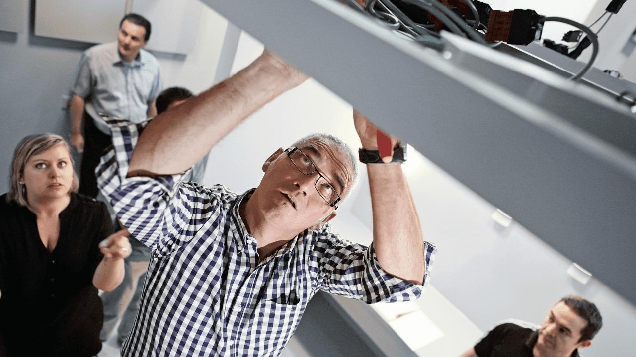 Mann montiert Sensor an der Decke