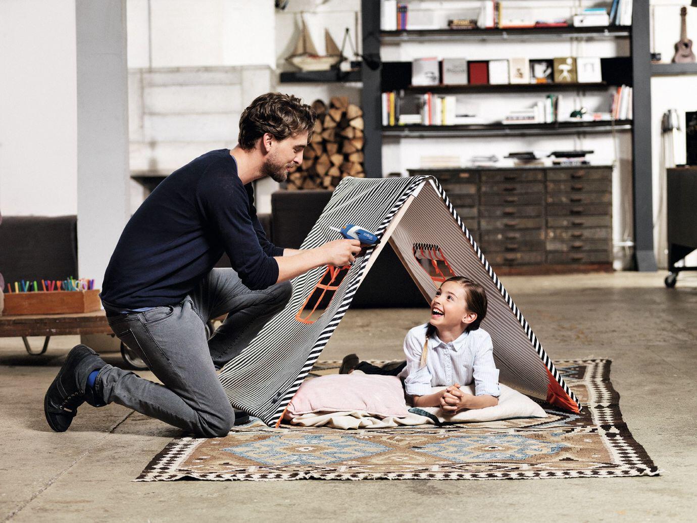 Vater und Tochter bauen ein Zelt aus Stoff mithilfe der Heißklebepistole neo2