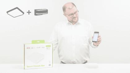 Mann zeigt Handy mit App und de Smart Friends Produkt