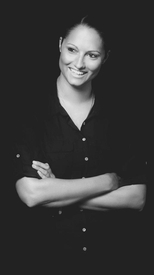 Frau in schwarzer Bluse lächelt mit verschränkten Armen